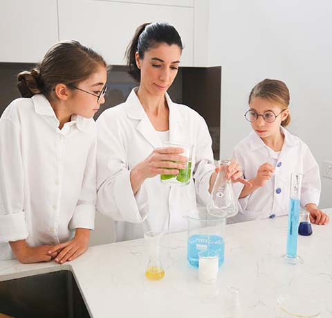 Nadine and two daughters wearing lab coats pouring liquid into scientific glassware in chemistry lab